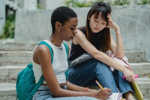 Two student sitting on a sidewalk looking at a notebook.